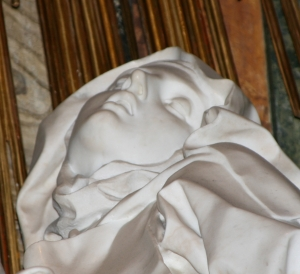 Close-up of marble statue--head of St. Teresa, leaning back, eyes closed. Wearing a head covering.